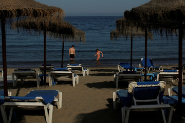 A couple cools off at the Mediterranean Sea during a hot spring day on Nueva Andalucia beach in Marbella