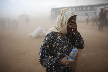A Kurdish Syrian refugee covers her face as she waits for transport during a sand storm on the Turkish-Syrian border near the southeastern town of Suruc