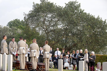 Family members of a British Royal Air Force crew who died in an aircraft crash during World War II recite prayers during a reburial ceremony in Kuala Lumpur