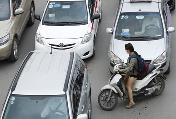 A woman rides a motorcycle among cars along a street in Hanoi