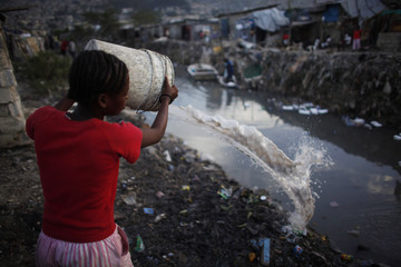 A resident throws dirty water into a drain which leads into the sea in Port-au-Prince