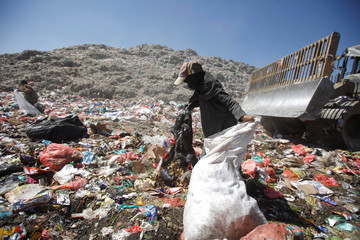 Girl collects recyclable items at a rubbish dump site on the outskirts of Sanaa