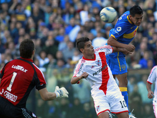 Boca Juniors' Monzon heads the ball over River Plate's Lamela and towards River Plate's goalkeeper Carrizo resulting in Carrizo's own goal during their Argentine First Division soccer match in Buenos Aires