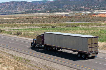 Dark Classic semi truck and trailer on the road with nature view