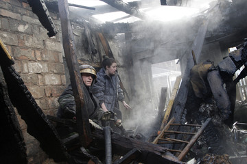 A woman and a firefighter walk amidst the debris of a house, which according to locals was recently damaged by shelling, in Donetsk