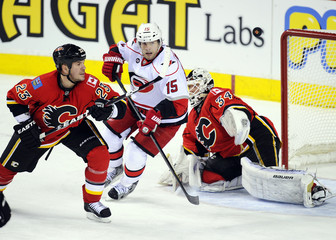 Calgary Flames' Hannan and Carolina Hurricanes' Ruutu chase the puck in front of Flames' Kiprusoff during their NHL hockey game in Calgary.