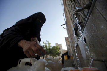 A woman fills jerrycans with clean water from a donated source amid an acute shortage of water supplies, in Yemen's capital Sanaa
