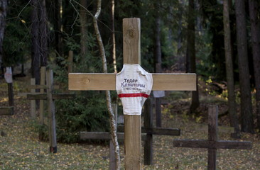 A cross with name of Belarussian writer Todar Klyashtorny is seen at a mass grave in Kuropaty
