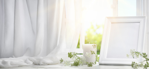 Picture frame near window with candle