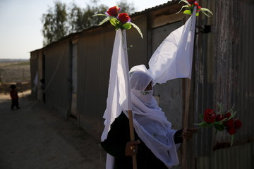 Harba, mother of Uda Tarrabin, holds decorations for a tent erected to welcome the release of her son, near Rahat in southern Israel