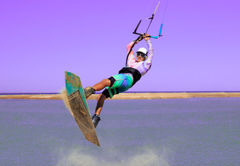 Professional kite boarding rider sportsman jumps high acrobatics kiteboarding trick with front rotation from sand into water. Recreational activity and extreme active water sports, hobby and fun time