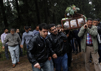 People carry a coffin of a victim killed in yesterday's car bombings in the town of Reyhanli of Hatay province near the Turkish-Syrian border
