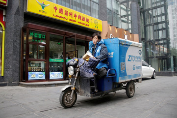 A deliveryman rides a vehicle with the logo of ZTO Express in Beijing