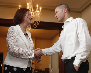 Australia's Prime Minister Gillard welcomes Australia's Clarke to an afternoon tea for Ashes team members in Sydney
