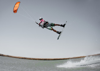 Professional kite boarding rider sportsman jumps high acrobatics kiteboarding raley trick  with water splash. Kitesurfer flies high. Recreational activity and extreme active water sports, hobby, fun