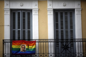 The photo of LGTB rights activist and Spanish Socialist politician Pedro Zerolo hangs next to a black ribbon on a rainbow flag in the quarter of Chueca in Madrid