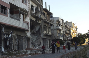 Civilians walk along a street near damaged buildings in the besieged area of Homs