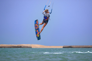Kitesurfing girl in sexy swimsuit with kite in blue sky on kiteboard in the blue sea jumping air trick. Recreational activity, water sports, action, hobby and fun in summer time. Kiteboarding sport