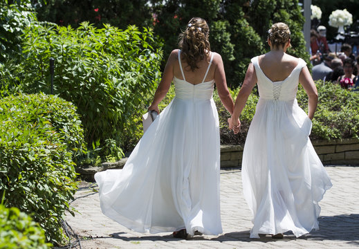 """A couple walks down a pathway to the """"The Celebration of Love"""", a grand wedding where over 100 LGBT couples will get married, at Casa Loma in Toronto"""