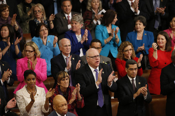 Democratic members of Congress rise and applaud President Barack Obama during his State of the Union address to a joint session of Congress in Washington