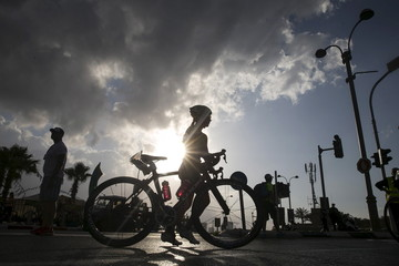 A participant stands as she is about to start the the cycling section of the Herzliya Women's Triathlon, near Tel Aviv