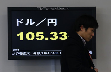 An employee walks past a screen displaying the Japanese yen's exchange rate against the U.S. dollar in Tokyo