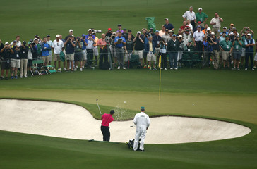 Tiger Woods of the U.S. hits from a sand trap onto the second green during his practice round ahead of the 2015 Masters at the Augusta National Golf Course in Augusta