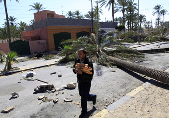 A man carries bread past a palm tree used as a roadblock by anti-Gaddafi demonstrators in Tripoli