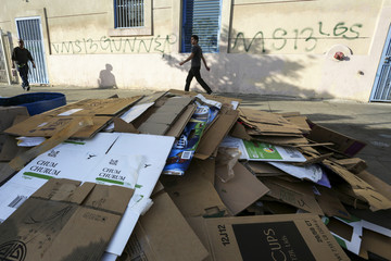 """People walk past a pile of cardboard boxes for recycling in Koreatown, a neighborhood designated as a """"Promise Zone"""" in Los Angeles, California"""