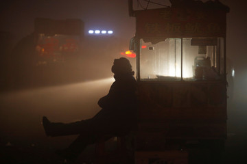 A street food vendor waits for customers as heavy smog blankets Shengfang, in Hebei province, on an extremely polluted day with red alert issued