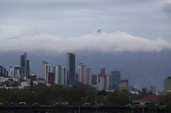 Cerro de la Silla mountain is seen in the background during cloud cover over Monterrey skyline after a rare snow storm fell in early hours on the outskirts of Monterrey