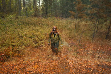 A firefighter, covered in fire retardant dropped from an airplane, exits the forest while battling the Twisp River fire near Twisp, Washington