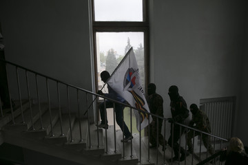 Mask pro-Russian activists carry a flag to the top of a government building in Donetsk