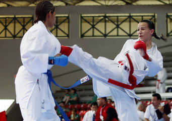 Micheo kicks her opponent Rodriguez during karate classifications at the Central American and Caribbean Games in Mayaguez