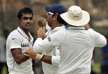 India's Mithun is congratulated by teammates after taking the wicket of Sri Lanka's Dilshan in Galle