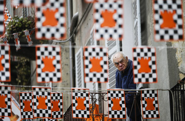 A man watches from his window as members of rival teams prepare to fight with oranges during an annual carnival battle in the northern Italian town of Ivrea