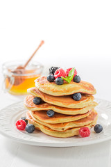 Delicious american pancakes with maple syrup and berries