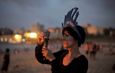 A woman wearing a 2017 hat shoots a video of the first sunrise of 2017 at Bondi Beach following new year celebrations in Australia's largest city