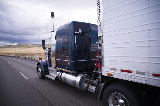 Custom big rig dark blue semi truck with reefer trailer