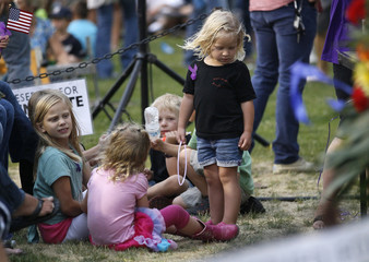 Children in the section reserved for immediate family of the 19 firefighters killed in a nearby wildfire play before a prayer vigil ceremony in Prescott