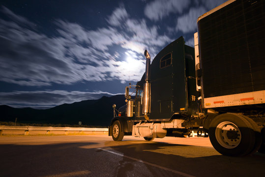 Dark semi truck reefer in night light with moony clouds