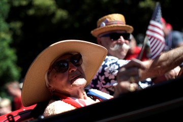 100-year-old Mary Dutra waves an American flag as she rides in an antique car through Barnstable Village, on Cape Cod during July 4th parade