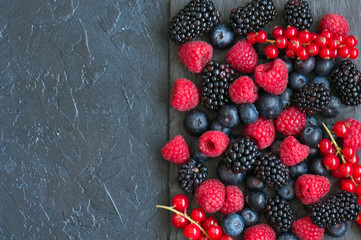 Berry raspberries red currants and blueberries on black slate board. Gray stone background.  Top view.