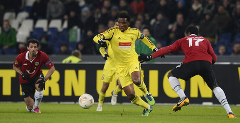 Anzhi Makhachkala's Samuel Eto'o and Hanover 96's Sergio Pinto and Johan Djourou fight for the ball during their Europa League soccer match in Hanover