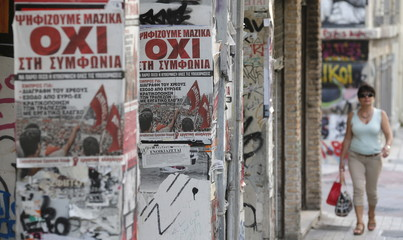 A woman makes her way past referendum campaign poster with the word 'No' in Greek in Athens