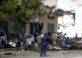 Somali policemen and soldiers are seen at the scene of the afternoon blast near Al Kowsar supermarket in the capital Mogadishu