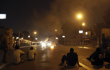 Protesters, who oppose Egyptian President Mohamed Mursi, make a fire to block a road during clashes with riot police in front of the presidential palace in Cairo