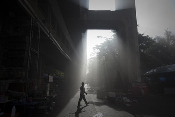 An anti-government 'red shirt' supporter walks through smoke under the sky train line near Central World shopping mall in Bangkok
