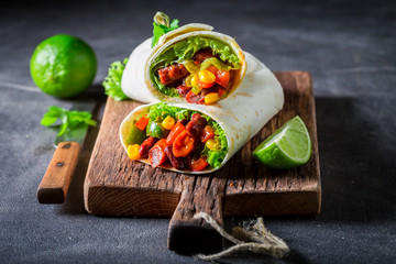 Tasty burrito with vegetables, spicy salsa and lime