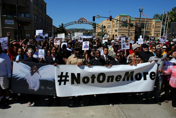 Demonstrators hold a march and rally to protest the fatal police shooting of Ugandan immigrant Alfred Olango in El Cajon, California